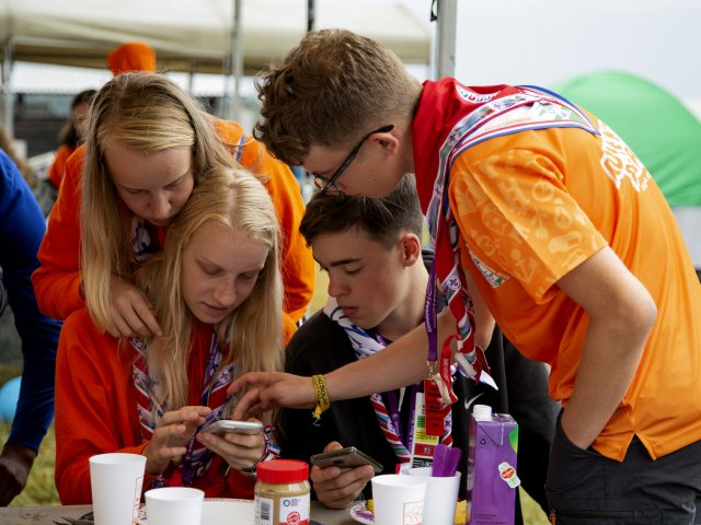 Four Scouts at World Scout Jamboree Using Phone New Digital System