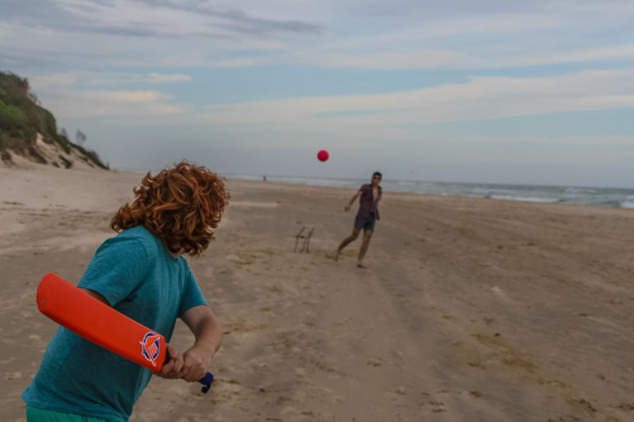 Two Adults Playing Beach Cricket