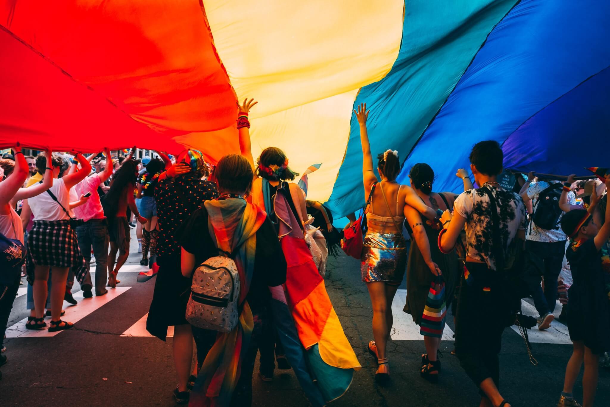 Parade Marchers Under Rainbow Flag Gender Diverse Members
